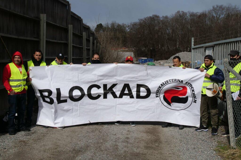 """Åtta personer står på rad och håller i en banderoll med texten """"blockad""""."""
