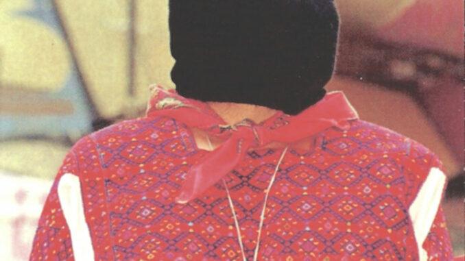 En bild som visar en person med röda kläder och svart huva som täcker huvudet.