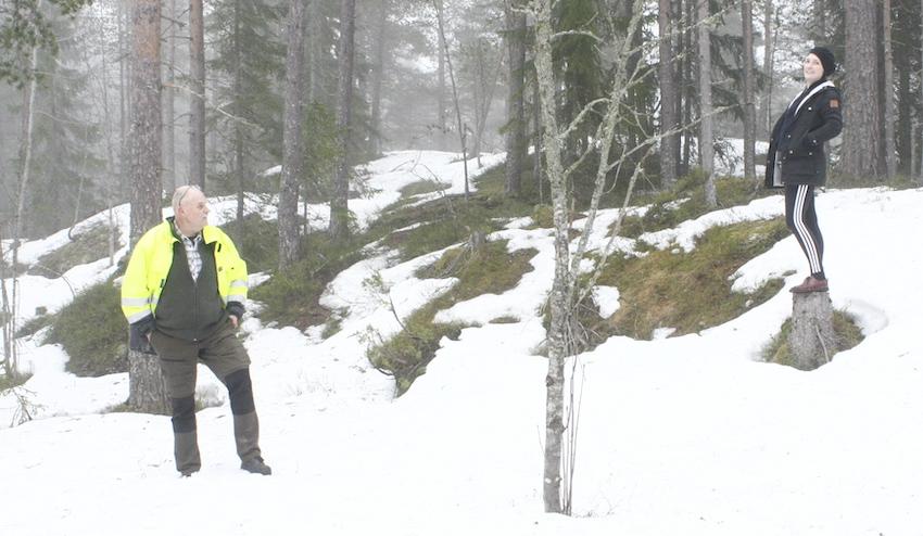 En person står i snö i en skog. En annan person står en bit ifrån på en stubbe.