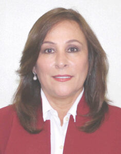 Foto på energiministern i Mexiko. Hon har långt mörkbrunt hår, pärlörhänge, vit skjorta och röd kavaj.