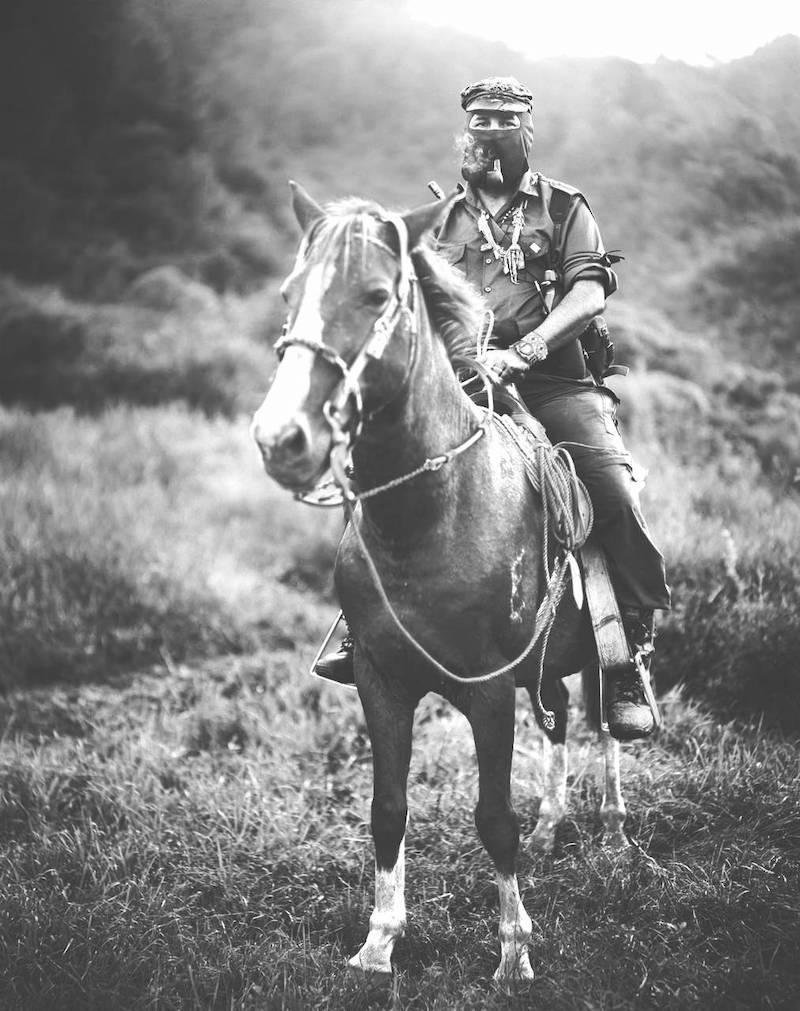 Svartvitt foto med en människa som sitter på en häst. Personen har på sig en mask och en keps. I bakgrunden synd växtlighet och berg.