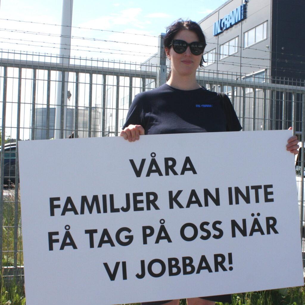 """En person står framför en stor lagerbyggnad och håller i en skylt med texten """"Våra familjer kan inte få tag på oss när vi jobbar!"""""""