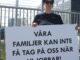"""En person står utanför en stor lagerlokal med ett plakat ed texten """"våra familjer kan inte få tag på oss när vi jobbar!"""""""