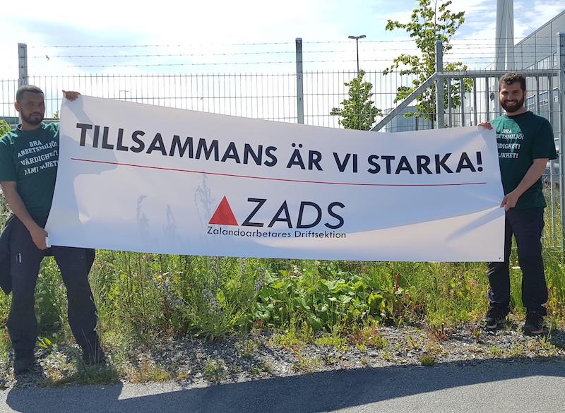 Två personer håller i en banderoll med texten Tillsammans är vi starka, ZADS, Zalandoarbetares driftsektion.