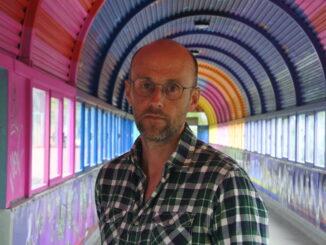 Halvbild på Pelle Sunvisson som står i en färgglag tunnel.