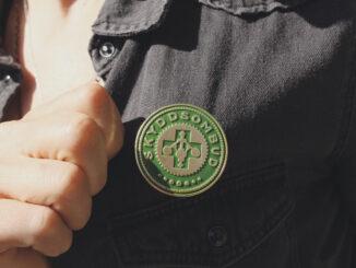 En hand håller tag i en skjorta för att visa sitt skyddsombudsmärke som sitter på skjortan.